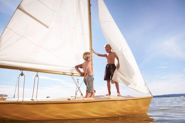Gutt ombord i en båt. re:member reward gir deg rabatter på dine reiser.